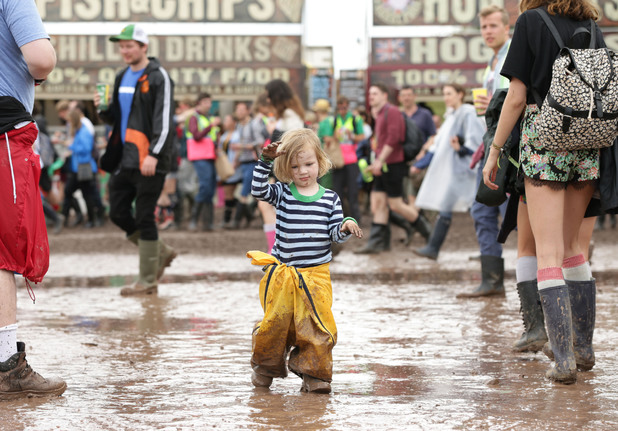 Two-year-old Julia Bristow from Iowa walks through a puddle of mud at Glastonbury Festival 2014