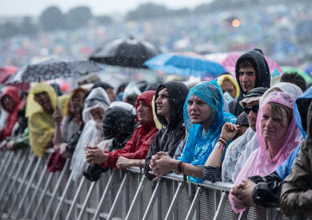 The crowd endure a downpour during the Glastonbury Festival at Worthy Farm on June 28
