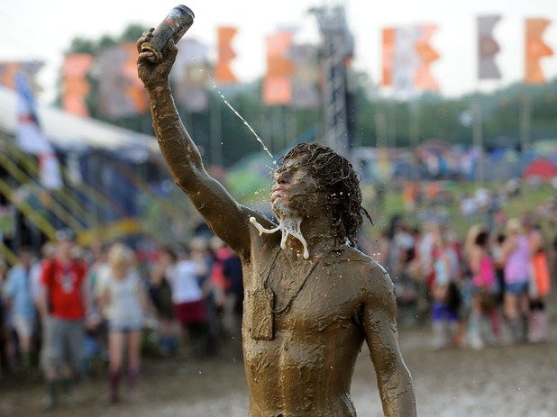 A festival goer covered in mud after wrestling with his friend at the 2009 Glastonbury Festival at Worthy Farm in Pilton, Somerset.