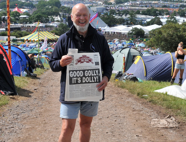 Festival organiser Michael Eavis poses with a copy of the Glastonbury Free Press during day three of the Glastonbury Festival