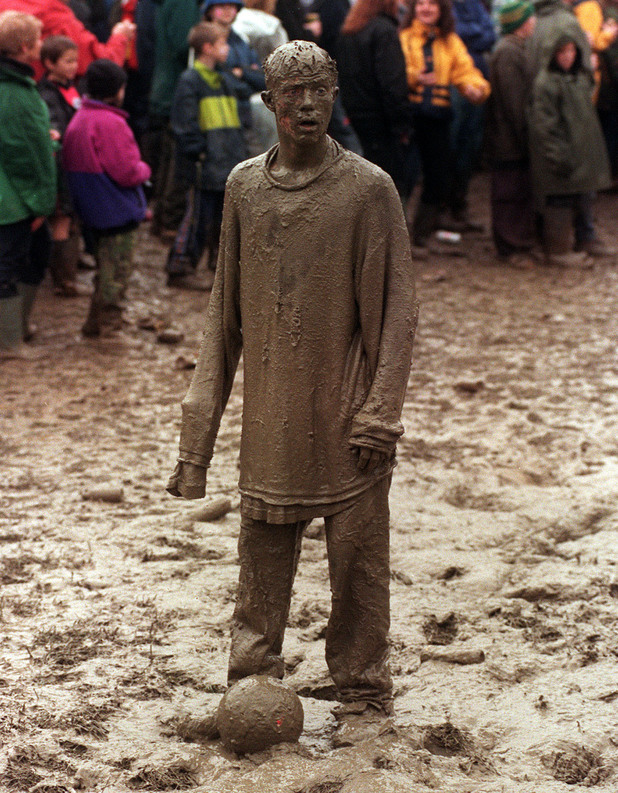 A MUD COVERED FESTIVAL GOER PLAYING FOOTBALL, AT THE RAIN DRENCHED GLASTONBURY FESTIVAL. Picture date: June 27th, 1998.