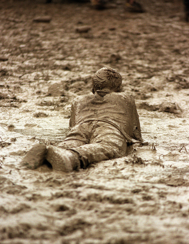 PA NEWS PHOTO 27/06/98 A FESTIVAL GOER ROLLS IN THE MUD DURING A GAME OF FOOTBALL, AT THE RAIN DRENCHED GLASTONBURY FESTIVAL.