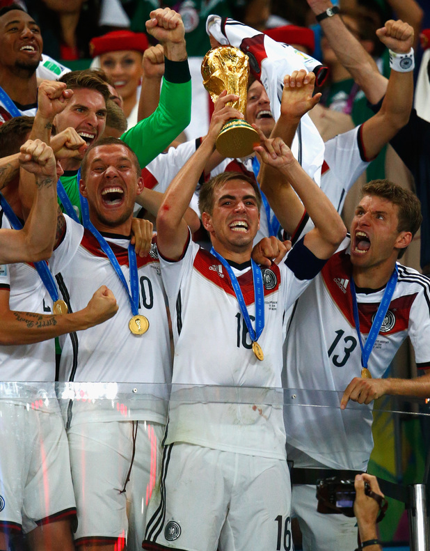 Philipp Lahm of Germany lifts the World Cup trophy with teammates after defeating Argentina 1-0 in extra time