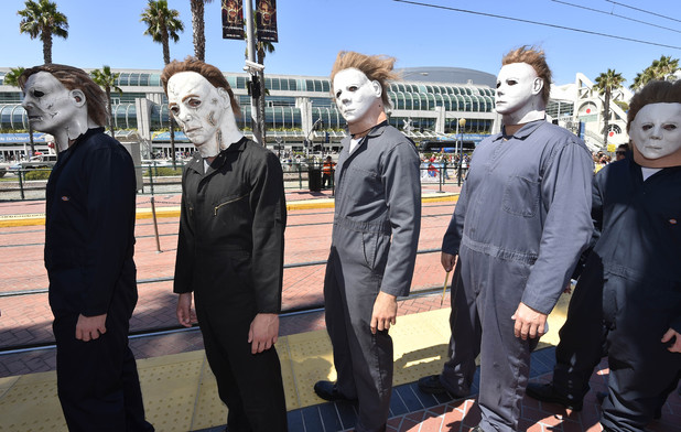 People dressed as serial killers from 'Halloween' wait outside the convention center on day 1 of the 2014 Comic-Con International Convention