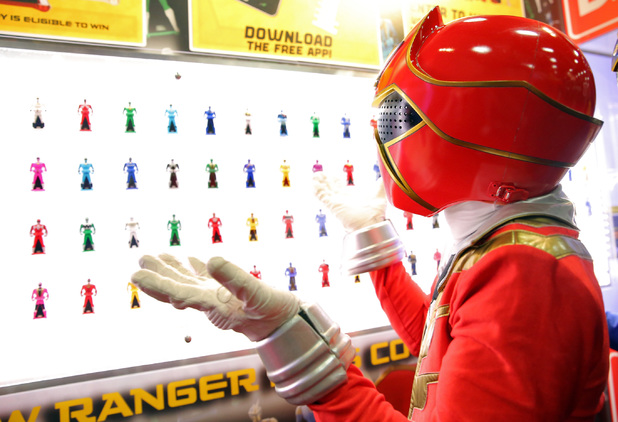 The Super Megaforce Red Ranger checks out the Legendary Ranger Keys at the Bandai America booth during Comic-Con International 2014