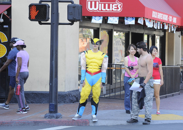 A fan dressed as Wolverine from the X-Men waits at a crosswalk on day 1 of the 2014 Comic-Con International