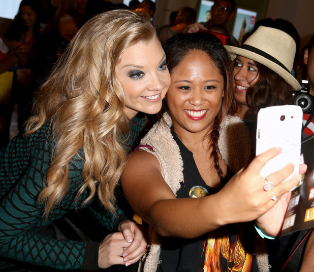 Natalie Dormer takes a selfie with a fan during the Samsung and Lionsgate premiere of the first official teaser trailer for The Hunger Games: Mockingjay - Part 1.