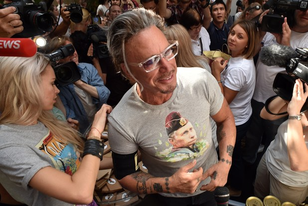US actor Mickey Rourke (C) stands in front of journalists as he puts on a T-shirt with the portrait of Russia's President Vladimir Putin in central Moscow on August 11, 2014. The sale of a new collection of T-shirts with Putin's portrait starts in the Russian capital on August 11, at a price of 1200 rubles (25 euros). AFP PHOTO / KIRILL KUDRYAVTSEV (Photo credit should read KIRILL KUDRYAVTSEV/AFP/Getty Images)