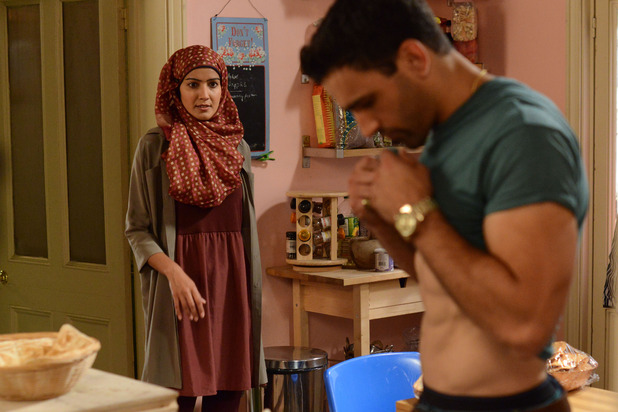 Kush lift his T-shirt to clean a drop of curry that has just fallen onto it, when Shabnam comes into the kitchen